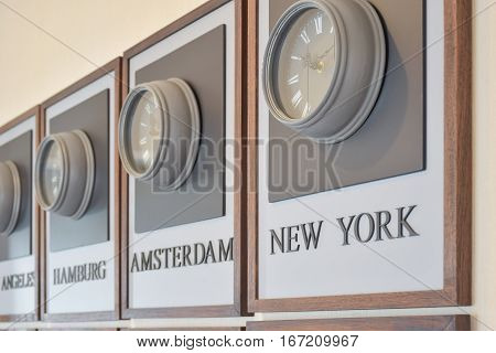 wooden clocks showing the time in different cities of the world on the wall