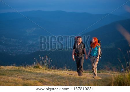 Couple Hikers With Backpacks Holding Hands, Walking In The Mountains