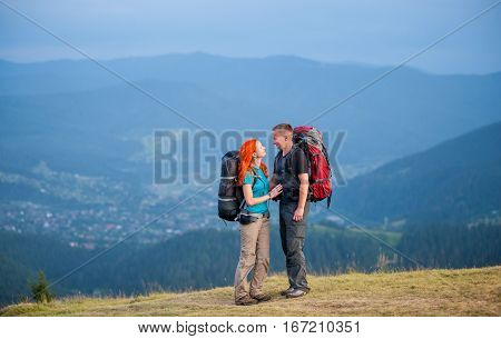 Tourist Couple With Backpacks On The Road In The Mountains