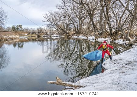 winter stand up paddling on the Poudre River in Fort Collins, northern Colorado -senior male paddler is launching his board from an icy shore