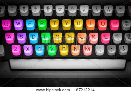 old typewriter with colorful keys on dark gray background.