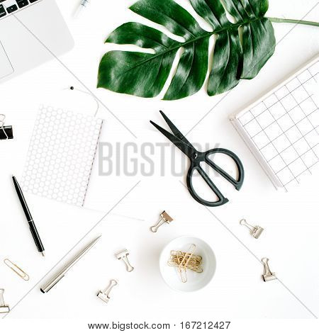 Home office workspace mockup with laptop scissors palm leaf notebook and accessories. Flat lay top view