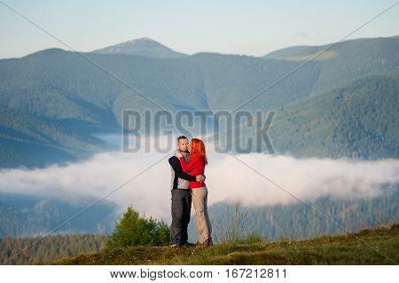 Romantic Couple Enjoying A Morning Haze Over The Mountains