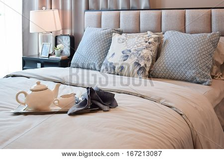 Elegant Bedroom Interior Design With Floral Pattern Pillow And And Decorative Tea Set On Bed