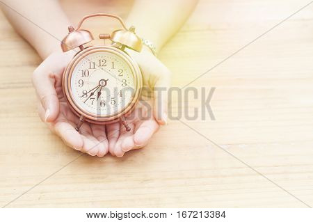 clock in hand on wood table with copy space concept in time for life and business