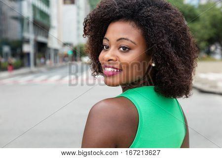 Beautiful woman from Africa looking back in city