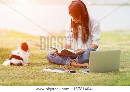 woman sitting on grass reading book and listen music