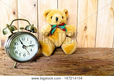 Old vintage alarm clock with bells, Brown Bear and old wooden background.