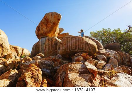 A tourist explores rock formations in the Pibara region of Western Australia, Australia. Exploring granite boulders.