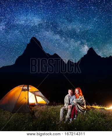 Sweety Couple Tourists Covered With A Plaid Sitting Together Near Campfire And Shines Tent At Night