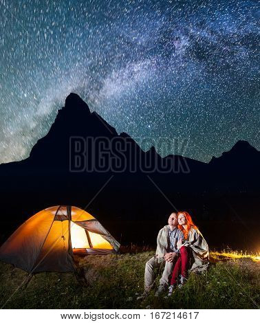 Two Lovers Hikers Sitting Together Near Campfire And Shines Camp At Night Under Stars And Looking To