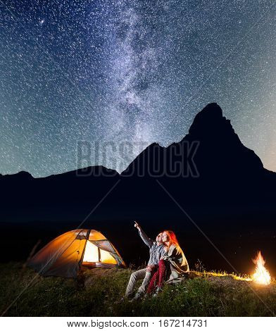 Romantic Couple Is Sitting Near The Glowing Tent And Campfire And Looking To The Stars In The Night