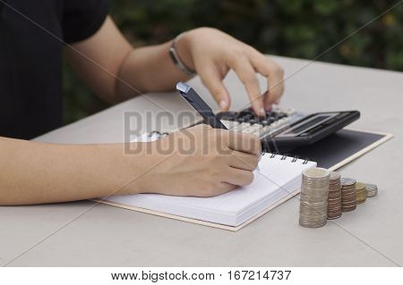 hand financial pile stack finance business desk writing tax office accounting calculating report paper money banking calculator coin close-up growth pen budget accountant businessman closeup working bank cost counting coins worker save payment advisor peo