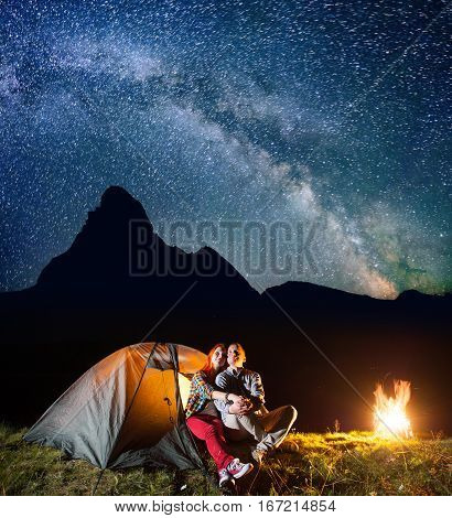 Two Tourists Looking To The Shines Starry Sky And Milky Way Near Shining Tent In The Camping At Nigh