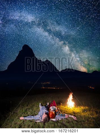 Twain Lovers Admiring Incredibly Beautiful Starry Sky And Milky Way And Lying Near The Bonfire At Ni