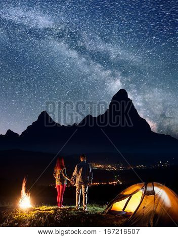 Night Camping. Romantic Tourist Couple - Girl And Guy Holding Hands, Standing Near Camp And Enjoying