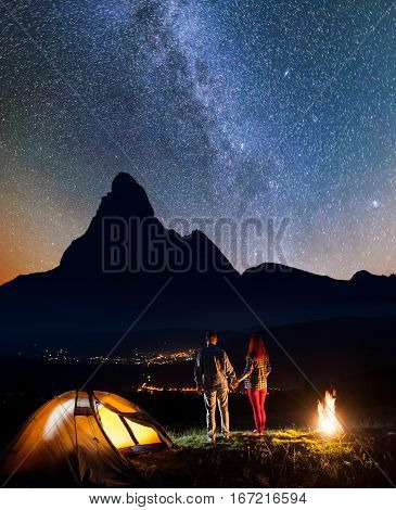 Charming Couple Backpackers Holding Hands, Standing Near Campfire And Enjoying Starry Sky