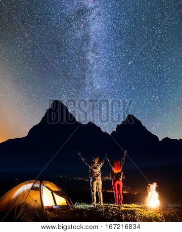 Young Romantic Couple - Guy And Girl Raised Their Hands Up Under The Stars Near Campfire And Tent