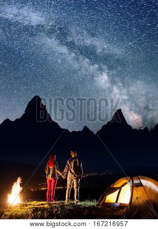 Rear View Tourist Couple - Girl And Guy Holding Hands, Standing Near Camp And Bonfire, Enjoying Star