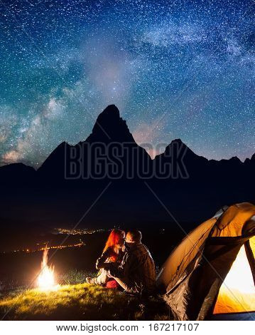Night Camping. Happy Couple Hikers Sitting And Kissing Near A Campfire And Tent Under The Stars And