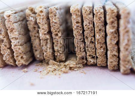 Grain crisp bread and crumbs closeup. Side view