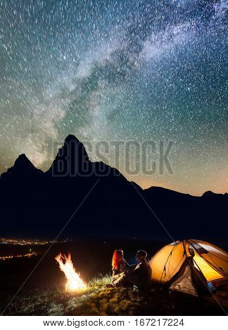 Tourist Family Sitting Face To Face In Front Tent Near Campfire Under Shines Starry Sky At Night. Lo