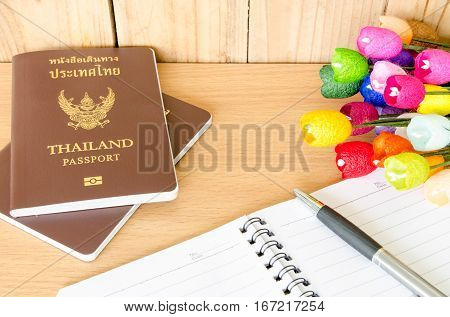 passport, notebook and pen on wooden table