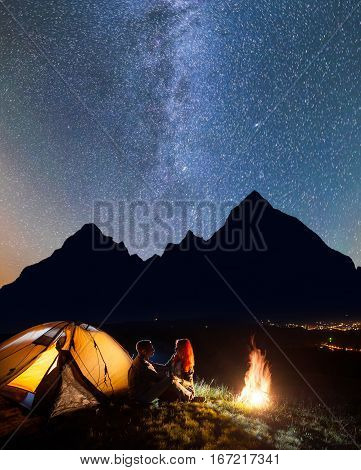 Happy Couple Hikers Sitting Face To Face In Front Tent Near Campfire Under Shines Starry Sky At Nigh