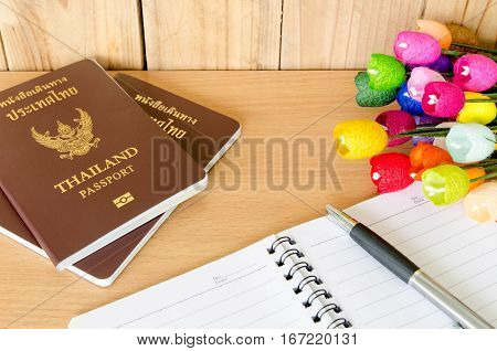 passport, notebook and pen on wooden table .