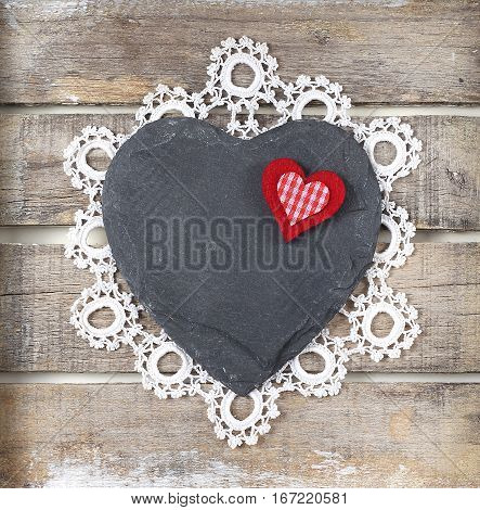 Stone heart and lace on old wooden background