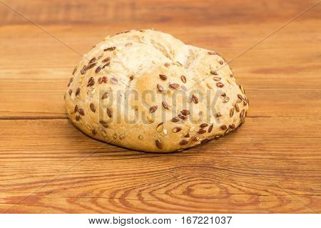 Round wheat sourdough bun sprinkled with flax and sesame seeds on an old wooden surface