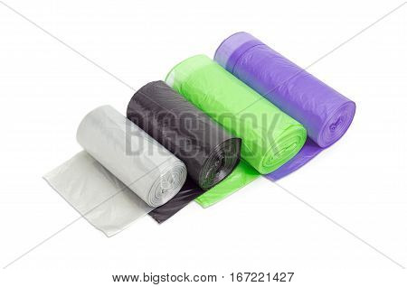 Several plastic disposable garbage bags of different sizes and colors in rolls including biodegradable and with handles made from ribbon which may be tied on a light background
