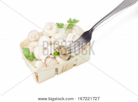 Half of the fried button mushroom with parsley leaf on the stainless steel fork on the background of blurred wooden basket with uncooked mushrooms on a light background