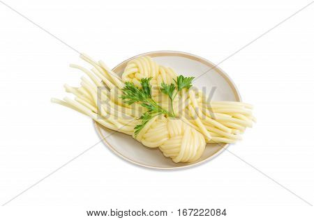 Two portions of the mozzarella cheese in the form of strings twisted in a shape of a plait and twig of parsley on the saucer on a light background
