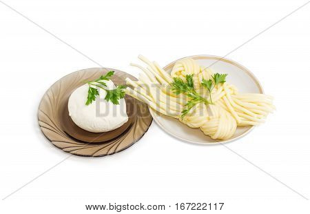 Ball of the fresh soaked mozzarella cheese on the glass saucer two portions of the mozzarella cheese twisted to form a plait on the other saucer and twigs of parsley on a light background
