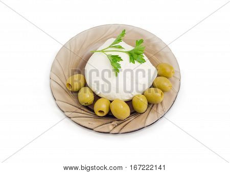 Ball of the fresh soaked mozzarella cheese with twig of parsley and several green olives on the glass saucer on a light background