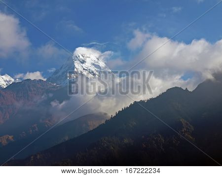 Mountain peak covered with glaciers against the backdrop of mountain ranges and the sky with clouds in the morning in the Himalayas