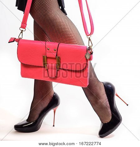 Beautiful Female Legs Inshoes On Red Stilettos And Pink Clutches