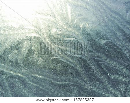 Frost patterns. white-blue frost on the glass. Winter patterned background. Winter composition. sprigs of frost on the glass. Winter patterns on glass.