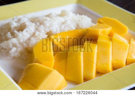 Thai dessert - mango with sticky rice - seved on the plate
