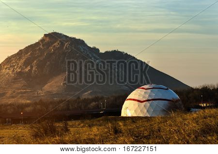 Galicia in the form of a dome on a background of the Caucasus Mountains in the sunset light