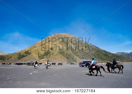 Horse riding through the sea of sand up to Mount Bromo summit
