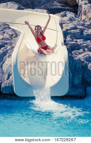 Blond Girl Riding Slide In Waterpark
