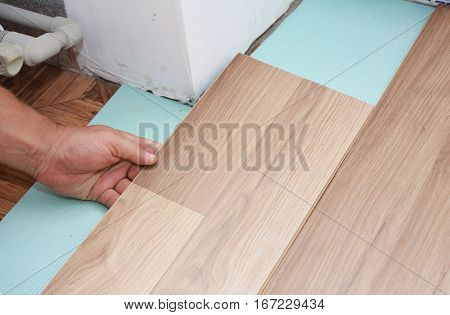 Man Installing New Laminate Wood Flooring in Problem Area.