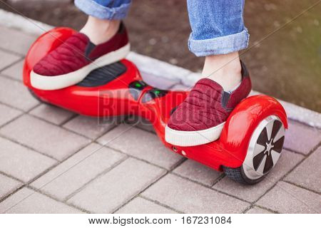 Feet of a gir in marsala shoes riding on modern red electric mini segway or hover board scooter. Trending new transportation technology that is so much fun and easy to ride and produces no air pollution to the atmosphere. Focus on the device