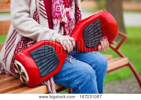 Girl in boho style clothes sitting on a bench holding modern electric mini segway or hover board scooter in hands. Trending new transportation technology that produces no air pollution to the atmosphere. Unrecognizable model and close up on the device