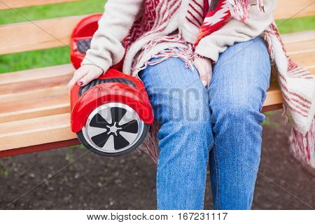 Woman in boho style clothes sitting on a benchwith modern electric mini segway or hover board scooter. Trending new transportation technology that is so much fun and easy to ride and produces no air pollution to the atmosphere. Focus on device