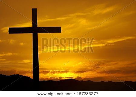 Silhouette of Christian cross at sunrise or sunset concept of religion