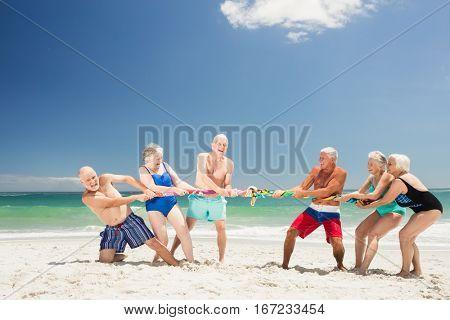 Senior friends playing tug of war on the beach