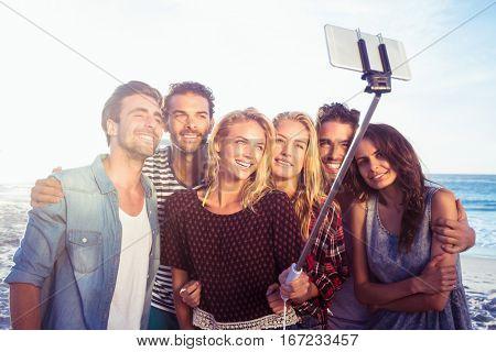 Happy friends taking selfie with selfie stick on the beach